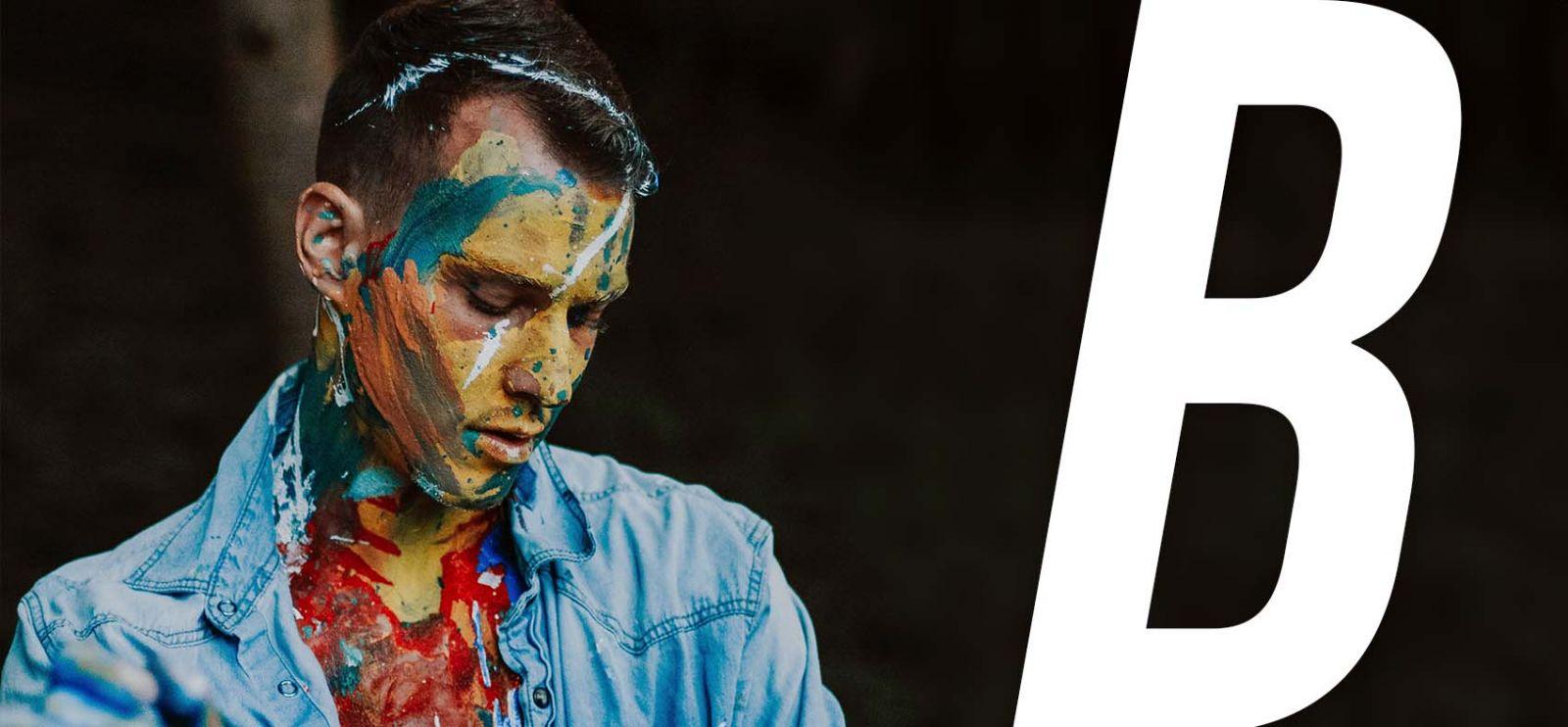 Csukott szemű és festékkel összekent arcú fiatal férfi.